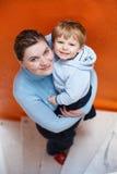 年轻母亲画象有她逗人喜爱小孩儿子微笑的。 免版税库存照片