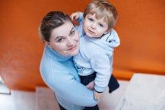 年轻母亲画象有她逗人喜爱小孩儿子微笑的 库存照片