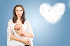 母亲画象有新出生的婴孩的有云彩背景 免版税库存照片