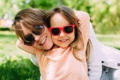 母亲画象有获得的女儿的乐趣 妇女和女孩在太阳镜的儿童孩子 免版税库存图片