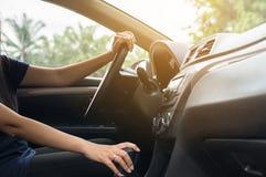 母司机的手在方向盘,驾驶在路的妇女的一辆汽车 免版税库存照片