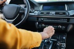 母在驾驶汽车前的司机转移变速杆的手 免版税库存图片