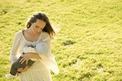 母性 有孩子的妇女在晴朗的夏日 免版税图库摄影