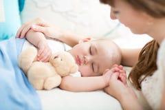 母性 父母身分 看她的婴孩的年轻母亲睡觉在床上 库存照片