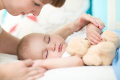 母性 父母身分 看她的婴孩的年轻母亲睡觉在床上 免版税库存照片