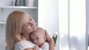 母爱,年轻父母在厨房体贴拿着他新出生的女孩然后拥抱并且亲吻 股票录像