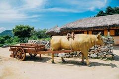 母牛在韩国老传统村庄拉扯木无盖货车 免版税库存图片