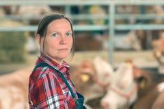 母牛奶牛场的女性农夫 免版税库存照片