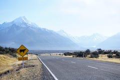 母牛路标有美好的山renge的新西兰路 免版税库存照片