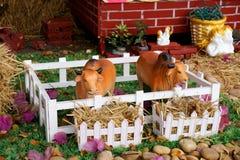 母牛陶瓷玩具在有六翼天使和丘比特背景的一个农场 免版税库存图片