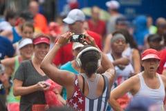 母赛跑者拍终点线的照片与智能手机的 免版税库存图片