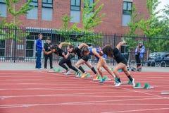 母高中赛跑者在100米种族把块留在 库存图片