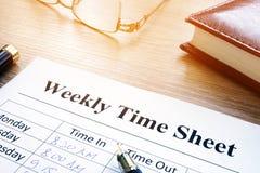 每周工时表和笔在书桌上 免版税图库摄影