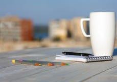 每天在木书桌上的日志构成有咖啡杯的 库存图片