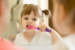 每天早晨看镜子的逗人喜爱的孩子女孩使用牙刷清洁牙在卫生间和夜里 免版税库存照片