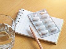 每次当采取药片,在天线罩包装的药片与笔记本和铅笔,耐心注意 图库摄影