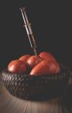 毒毒素的射入到一个有机蕃茄里 库存图片