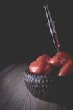 毒毒素的射入到一个有机蕃茄里 免版税库存图片