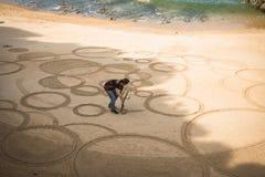 比亚利兹,法国- 2017年10月4日:在创造沙子图画的人艺术家的上部看法用在沙滩的木棍子 库存照片