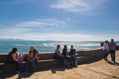 比亚利兹,法国- 2017年5月20日:坐下和享用春天温暖的太阳的人们在大西洋海岸线在晴朗的巴斯克国家 库存照片