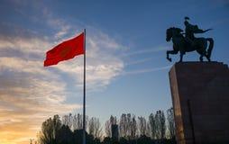 比什凯克,吉尔吉斯斯坦:玛纳斯的,古老吉尔吉斯epos的英雄纪念碑,与在比什凯克中央Al的全国吉尔吉斯斯坦旗子一起 免版税库存照片