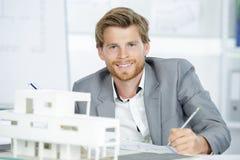 比例模型房子和愉快的建筑师 免版税库存图片