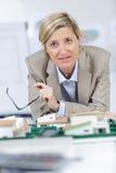 比例模型房子和愉快的建筑师妇女在背景中 库存照片