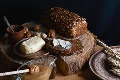 比切在桌上的面包和在树桩的木背景染黑在板、黄油和蜂蜜,亚麻籽的切的面包, 库存图片