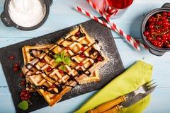 比利时华夫饼干板材用巧克力汁和无核小葡萄干在蓝色木背景结果实 从顶视图 图库摄影