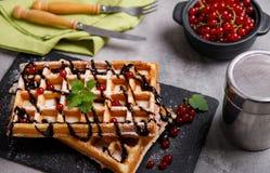 比利时华夫饼干板材用巧克力汁和无核小葡萄干在蓝色木背景结果实 从顶视图 库存图片