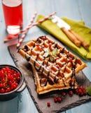 比利时华夫饼干板材用巧克力汁和无核小葡萄干在蓝色木背景结果实 从顶视图 免版税图库摄影