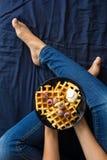 比利时华夫饼干用在蓝色陶瓷板材的奶油色和冷冻莓在妇女` s手上 图库摄影