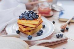 比利时华夫饼干用在轻的木桌上的蓝莓 健康早餐横向格式 免版税图库摄影