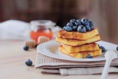 比利时华夫饼干用在轻的木桌上的蓝莓 健康的早餐 免版税库存图片
