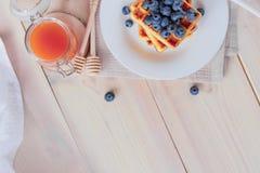 比利时华夫饼干用在轻的木桌上的蓝莓 健康的早餐 免版税库存照片