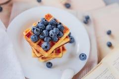 比利时华夫饼干用在轻的木桌上的蓝莓 健康的早餐 图库摄影
