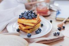 比利时华夫饼干用在轻的木桌上的蓝莓 健康的早餐 免版税图库摄影