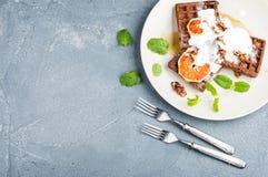 比利时软的奶蛋烘饼用血橙、奶油、marple糖浆和薄菏在白色板材 免版税图库摄影