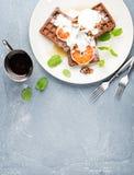 比利时软的奶蛋烘饼用血橙、奶油、marple糖浆和薄菏在白色板材 库存照片