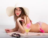 比基尼泳装、太阳镜和说谎在海滩毛巾的一个大帽子的美丽的女孩站立在一杯鸡尾酒旁边 库存照片