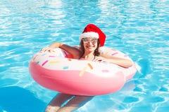 比基尼泳装和圣诞老人帽子的美丽的女孩有在蓝色游泳池的多福饼可膨胀的桃红色圈子的 库存照片