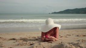 比基尼泳装和太阳帽子的少妇读书的,当晒日光浴在海滩时 股票视频