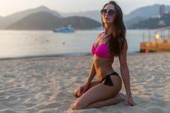 比基尼泳装和太阳镜的可爱的亭亭玉立的年轻深色的妇女坐与山的海滩微笑的赞赏的日出 库存图片