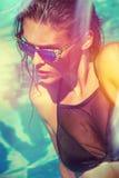 比基尼泳装和太阳镜的可爱的女孩在水池 库存照片