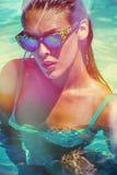 比基尼泳装和太阳镜的可爱的女孩在水池 免版税库存图片
