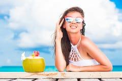 比基尼泳装和太阳镜的妇女有放松在热带海滩的新鲜的椰子鸡尾酒的 库存照片