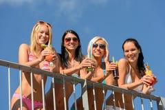 比基尼泳装的美丽的妇女微笑与饮料的 免版税图库摄影