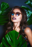 比基尼泳装和太阳镜的美丽的性感的妇女在热带植物中 秀丽,方式 温泉,医疗保健 热带假期 免版税图库摄影