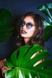 比基尼泳装和太阳镜的美丽的性感的妇女在热带植物中 秀丽,方式 温泉,医疗保健 热带假期 图库摄影