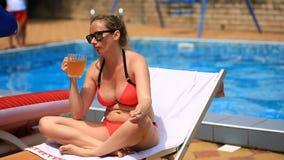 比基尼泳装和太阳镜的醉酒的大肚子妇女喝啤酒的由水池,抽香烟 股票录像